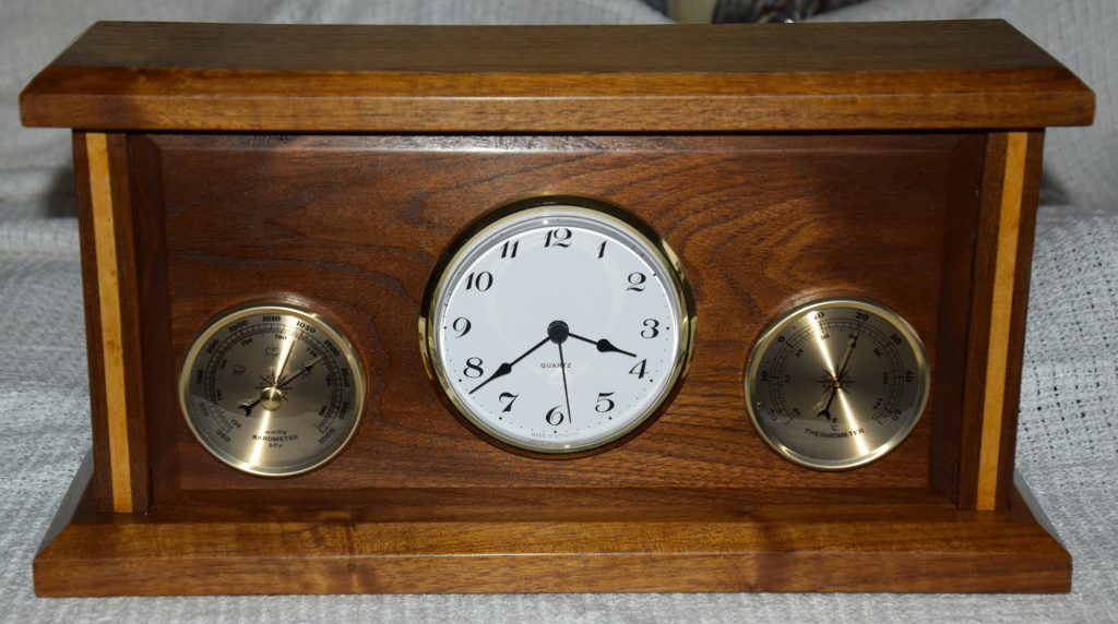 Three in one built on the Paul Sellars plan. This holds a Clock, Thermometer and Barometer. Made from American Black Walnut with Maple inlays on the uprights. FInished with standard French Polish and a final polish with Liberon Bison Wax